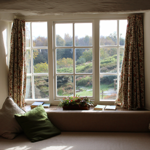 A scenic view of a large cosy window with pillows, cushions and books on the window sill.