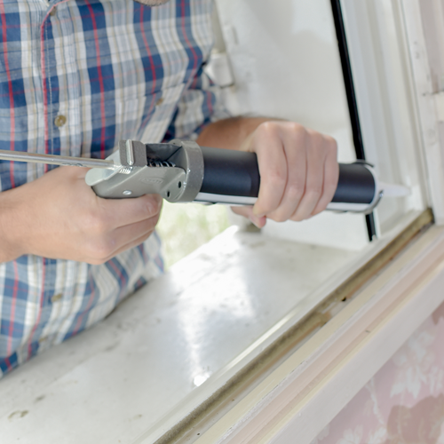 An image of a man applying glue or sealant to repair a window.