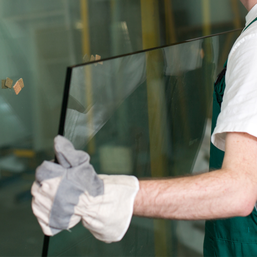 A picture of a man wearing gloves lifting a pane of glass.