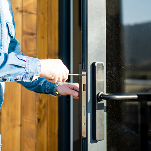 A picture of a man fixing a doors lock with a screwdriver.